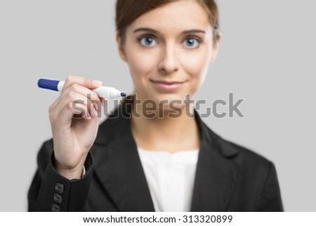 Beautiful businesswoman drawing on a glass board with a marker - stock photo