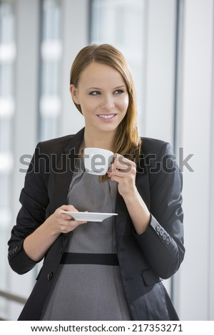 Beautiful businesswoman drinking coffee in office - stock photo