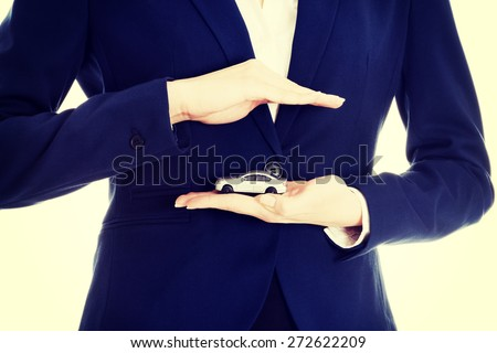 Beautiful businesswoman holding a model of car - stock photo