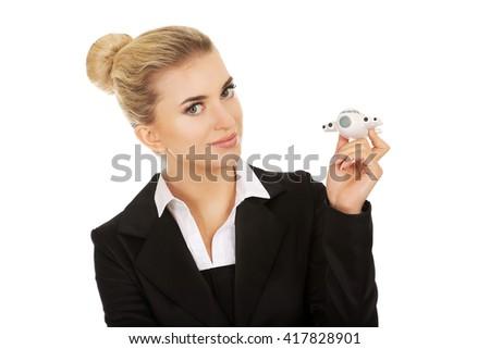 Beautiful businesswoman holding airplane miniature - stock photo
