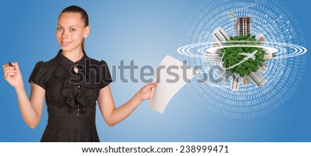 Beautiful businesswoman holding blank paper sheet and felt pen ready to use.  Beside is miniature Earth with trees, industrial and residential buildings, airplane and surrounded by rings., part of - stock photo