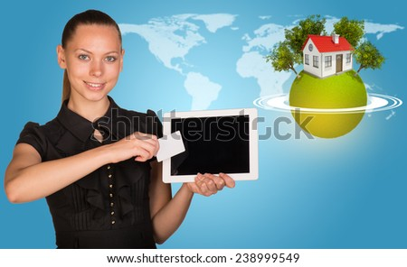 Beautiful businesswoman holding blank tablet PC and blank business card in front of PC screen. Green planet surrounded by horisontal rings, with house and trees on top, and world map as backdrop - stock photo