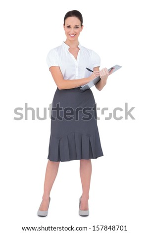 Beautiful businesswoman holding clipboard while posing on white background - stock photo