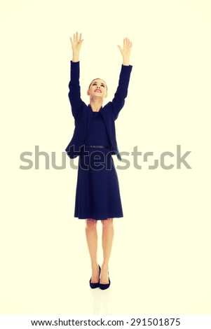 Beautiful businesswoman holding hands up - stock photo