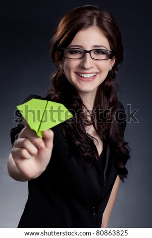 beautiful businesswoman  holding paper plane over black background - stock photo