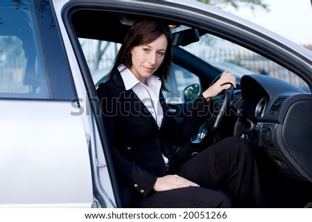 beautiful businesswoman in a silver car