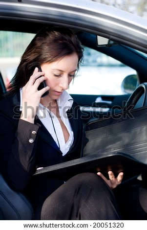 beautiful businesswoman in a silver car talking on cellphone - stock photo