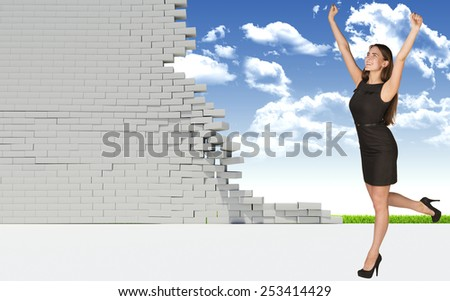 Beautiful businesswoman in dress happily raised his hands up, looking at camera. Dilapidated brick wall, green meadow and sky as backdrop. Concept of freedom - stock photo