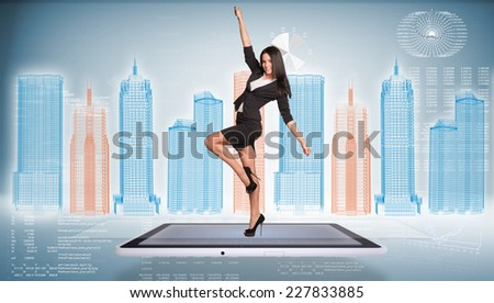 Beautiful businesswoman in jacket and skirt posing on screen of tablet pc. Wire-frame business city and graphs as backdrop