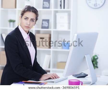 Beautiful businesswoman in office looking at camera,small depth of field