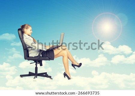 Beautiful businesswoman in suit sitting on office chair and holding open laptop, leaning back, smiling - stock photo