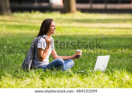 Beautiful businesswoman is drinking coffee and using laptop while resting from work at the park.Businesswoman drinking coffee and using laptop