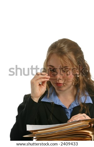Beautiful businesswoman looking at files and removing glasses - stock photo