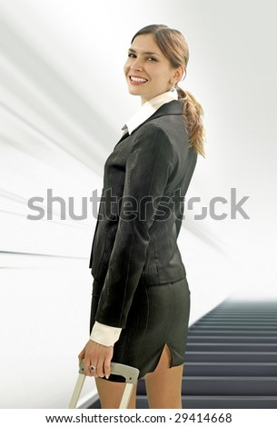 beautiful businesswoman moving by moving ramp in the airport - stock photo