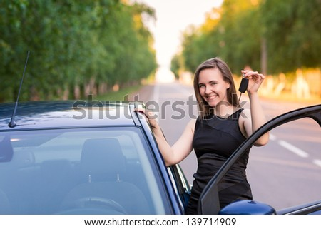 Beautiful businesswoman near her car on the road - stock photo