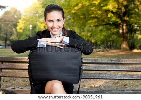 beautiful businesswoman on break in park with  cute smiling - stock photo
