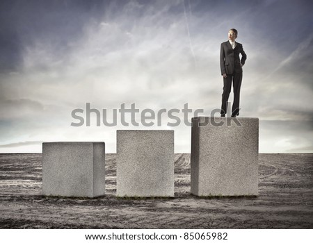 Beautiful businesswoman on the highest of three cubes - stock photo