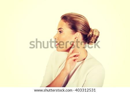 Beautiful businesswoman overhears a conversation - stock photo