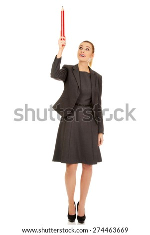 Beautiful businesswoman pointing up with pencil. - stock photo