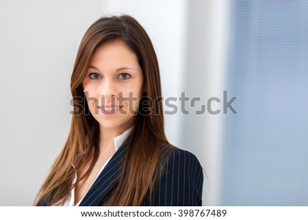 Beautiful businesswoman portrait in a bright office - stock photo