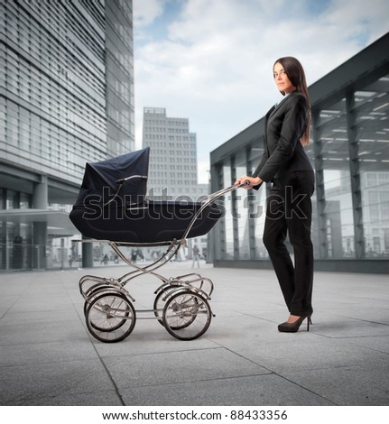 Beautiful businesswoman pushing a pram with office buildings in the background - stock photo
