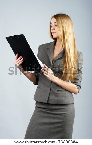 Beautiful businesswoman reads some documents in clipboard - stock photo