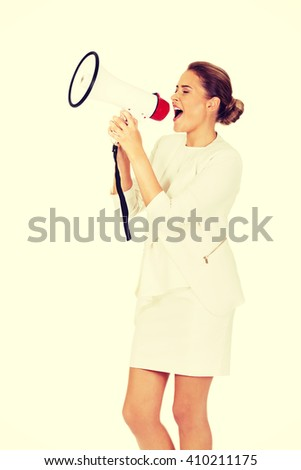 Beautiful businesswoman screaming through megaphone - stock photo