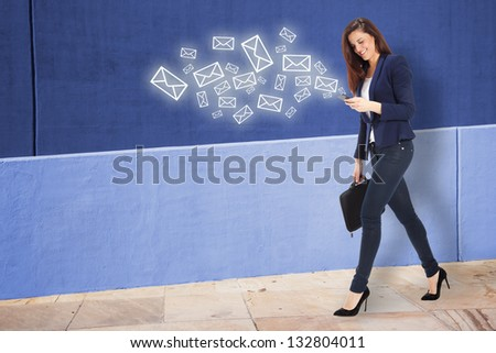Beautiful businesswoman sending a message on smart phone. Young businesswoman walking on the street - stock photo
