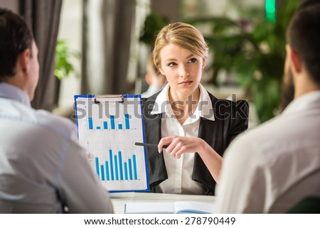 Beautiful businesswoman showing chart to her partners at business lunch. - stock photo