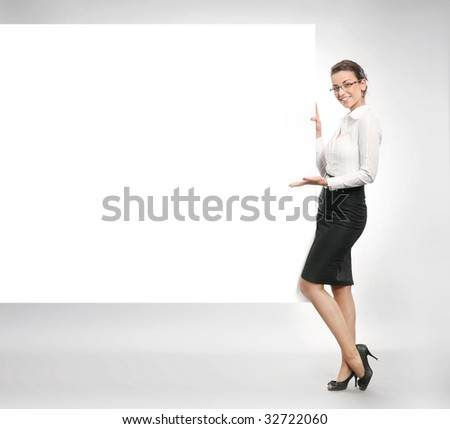 Beautiful businesswoman showing empty white board - stock photo