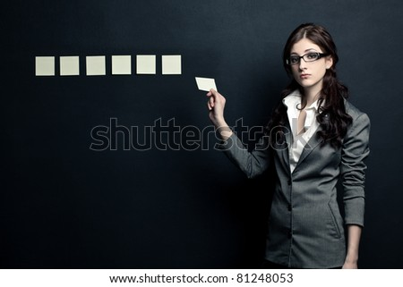 beautiful businesswoman showing stick-notes near black wall