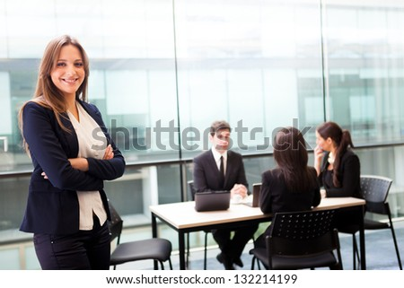 Beautiful businesswoman smiling with his colleagues behind - stock photo