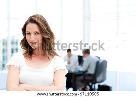 Beautiful businesswoman standing in front of her team while working in the background