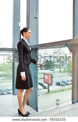 beautiful businesswoman standing inside her office building next bog window - stock photo