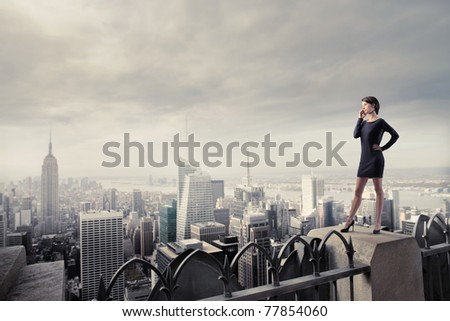 Beautiful businesswoman standing on the rooftop of a skyscraper over a city - stock photo