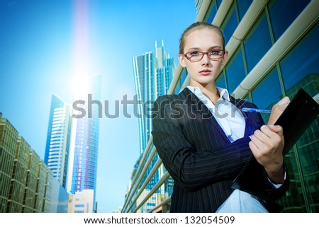 Beautiful businesswoman standing on the street of the big city.
