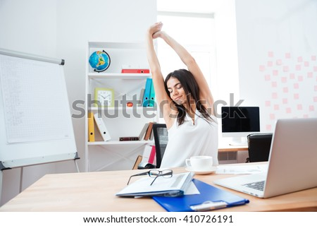 Beautiful businesswoman stretching hands in office - stock photo