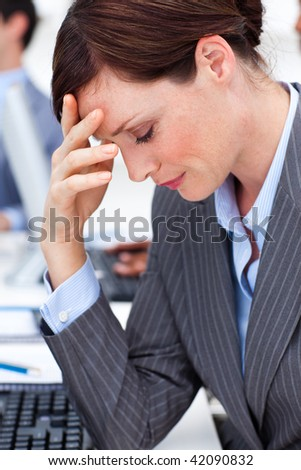 Beautiful businesswoman suffering from a headache in the office - stock photo