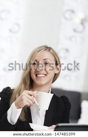 Beautiful businesswoman taking a coffee break smiling happily and enjoying a cup of hot espresso with copyspace above - stock photo