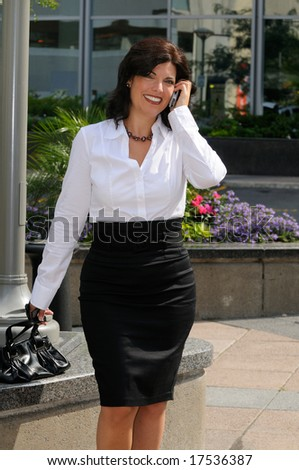 Beautiful Businesswoman Talking On Her Cellphone Outside The Office - stock photo