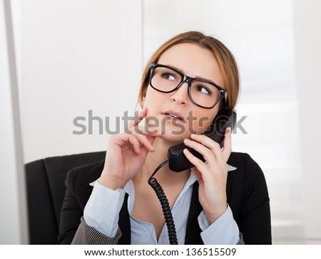Beautiful Businesswoman Talking On Telephone In Office - stock photo