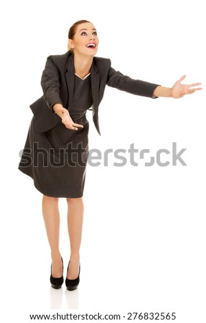 Beautiful businesswoman trying to catch something. - stock photo