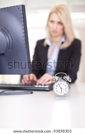Beautiful businesswoman trying to meet a deadline in the office - stock photo