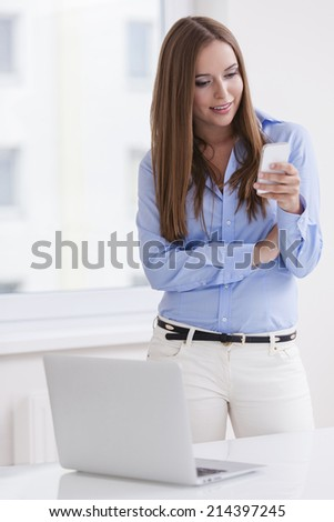 Beautiful businesswoman using cell phone - stock photo