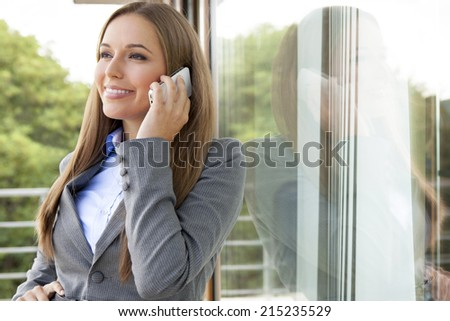 Beautiful businesswoman using cell phone by glass door - stock photo