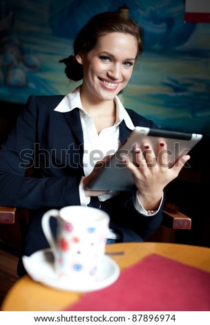 Beautiful businesswoman using tablet computer on coffee break. Selective focus.