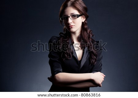 beautiful businesswoman  wearing glasses posing over black background