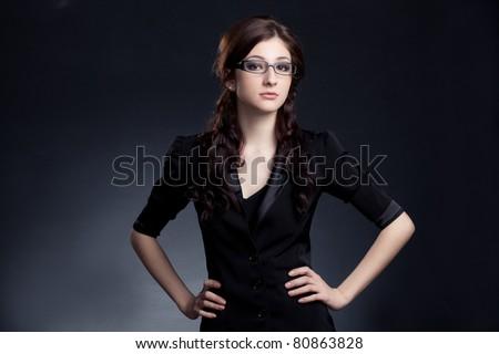 beautiful businesswoman  wearing glasses posing over black background - stock photo