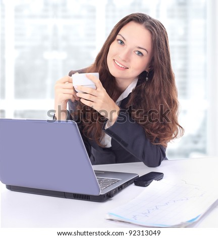 Beautiful businesswoman with a cup of coffee in the office.