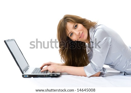 Beautiful businesswoman with a laptop lying on bed. White background